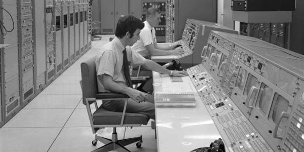 Two employees performing a data analysis in 1960s 1970s computer room