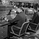 Two men programming on a large mainframe computer
